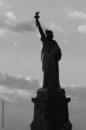 Silhouette of statue of Liberty in New York City at sunset - black and white