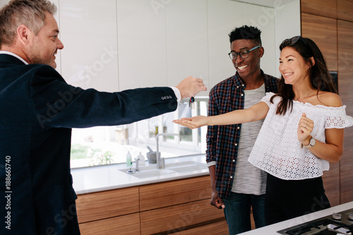 Photo  Estate agent handing over keys of new home to female buyer
