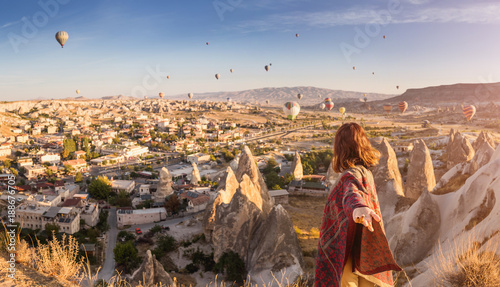 Foto auf Gartenposter Cappuccino A woman travels through Cappadocia at the background of a grandiose balloon show in Turkey