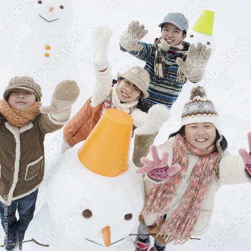 雪原に並ぶ雪だるまと子供たち