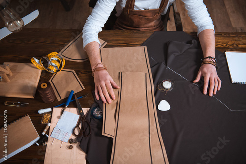 cropped shot of male fashion designer working with sewing patterns, tools and fa Fototapet