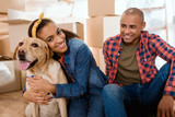 Fototapeta Zwierzęta - happy african american family with labrador dog moving to new apartment