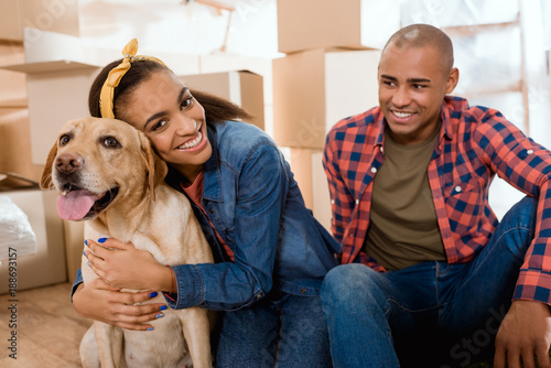 Photo happy african american family with labrador dog moving to new apartment