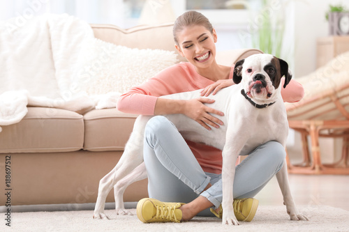 Photo Woman with cute white Boxer dog indoors. Pet adoption