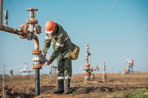 Fototapeta Oil worker is turning valve on the oil pipeline, oil deposit on the background. obraz