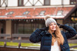Smiling blonde woman wearing black winter coat and knitted hat posing at the street in Kiev