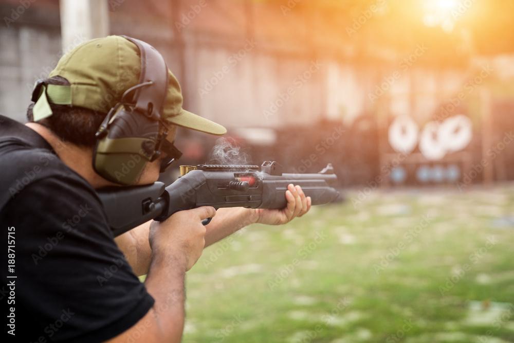 Fototapeta Man shooting on an outdoor shooting range, selective focus
