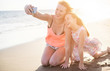 Happy mother and daughter taking selfie photo with smartphone on the beach - Mother having fun with her kid on holiday vacation - Family lifestyle concept