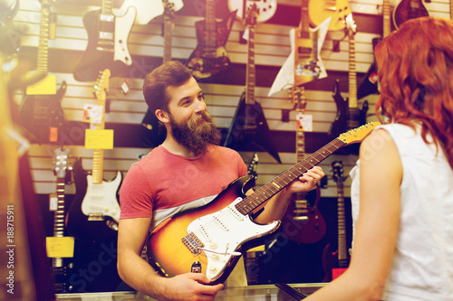 Keuken foto achterwand Muziekwinkel assistant showing customer guitar at music store
