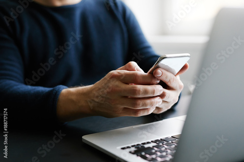 Man with mobile phone and laptop in office