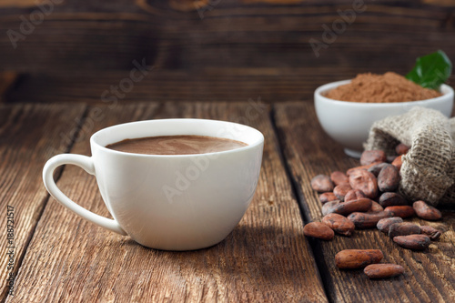 In de dag Chocolade Cocoa drink in white mug, cocoa powder and cocoa beans on wooden table.
