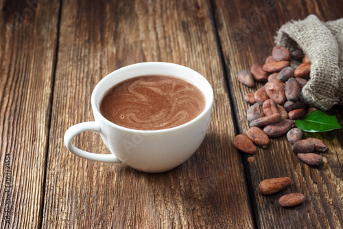 In de dag Chocolade Cocoa drink in white mug and cocoa beans on wooden table.