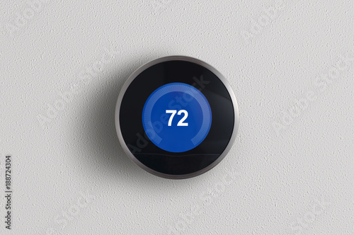 Fototapeta A simplistic photo of a round, modern, programmable digital thermostat in cooling mode, on a clean white wall. obraz
