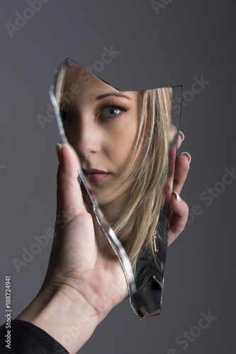 Fotomural Woman looking at her face in shard of broken mirror
