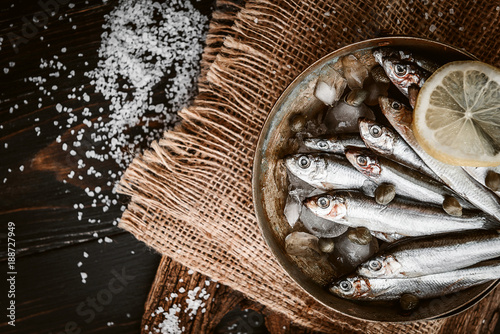 raw fresh fish on a silver platter with ice capers and lemon Canvas Print