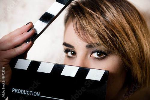 Photo  Pretty blonde young woman eyes behind movie clapper board