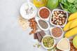 Leinwandbild Motiv Healthy food nutrition dieting concept. Banana, chocolate, spinach, avocado, apple, quinoa, chia, flax seeds, yogurt, almond, beans, oat, pumpkin seeds, olive oil. Top view, flat lay, copy space.