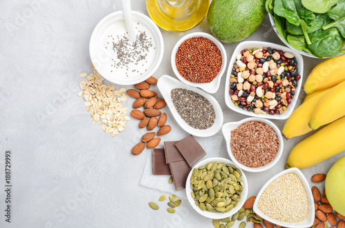 Fototapeta Healthy food nutrition dieting concept. Banana, chocolate, spinach, avocado, apple, quinoa, chia, flax seeds, yogurt, almond, beans, oat, pumpkin seeds, olive oil. Top view, flat lay, copy space. obraz