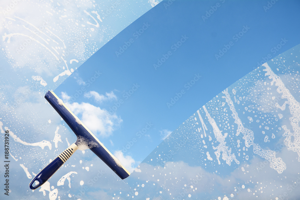 Fototapety, obrazy: Rubber squeegee cleans a soaped window and clears a stripe of blue sky with clouds, concept for tranparency or spring cleaning, copy space in the background