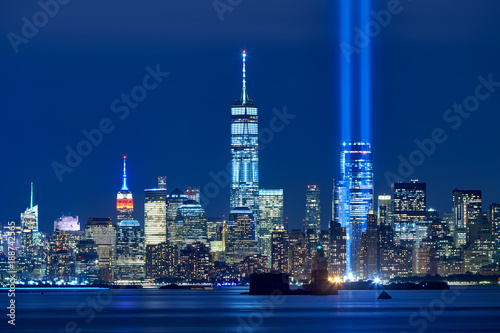 The two beams of the Tribute in Light with skycrapers of Financial District at night. Lower Manhattan, New York City