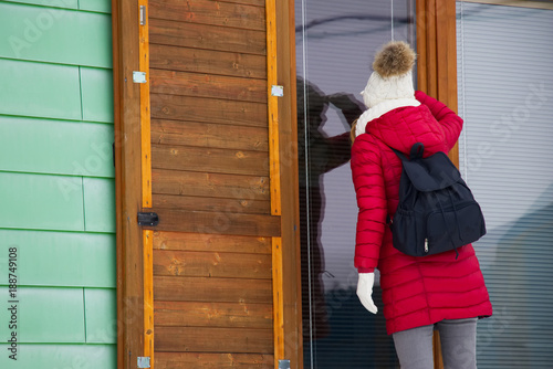 Photo Is anybody home? Woman is looking through the glassed door to the house