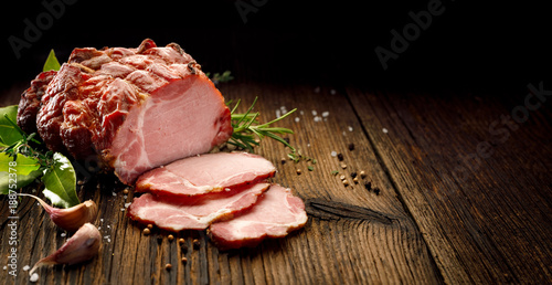 Garden Poster Meat Sliced smoked gammon on a wooden table with addition of fresh herbs and aromatic spices. Natural product from organic farm, produced by traditional methods