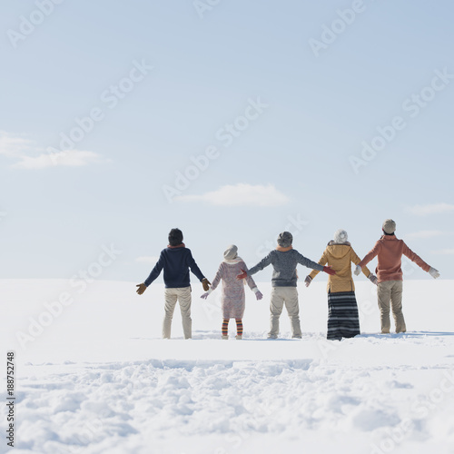 雪原で深呼吸をする若者たちの後姿