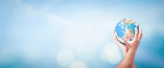 World environment day concept: Two human hands holding earth globe over blurred blue sky background. Elements of this image furnished by NASA.