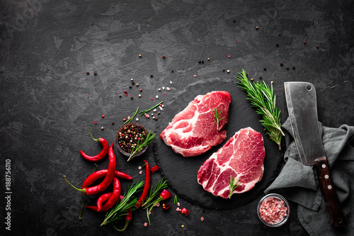 Papiers peints Viande Raw pork meat. Fresh steaks on slate board on black background. Top view