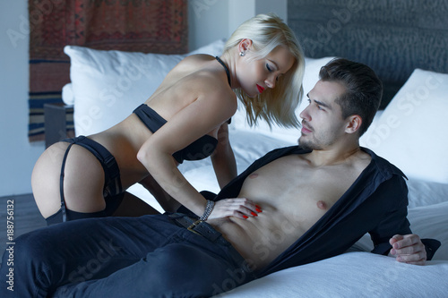 Fotografie, Obraz  Sexy woman in underwear playing with macho lovers abs on bed