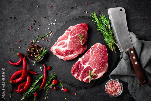 Door stickers Meat Raw pork meat. Fresh steaks on slate board on black background. Top view