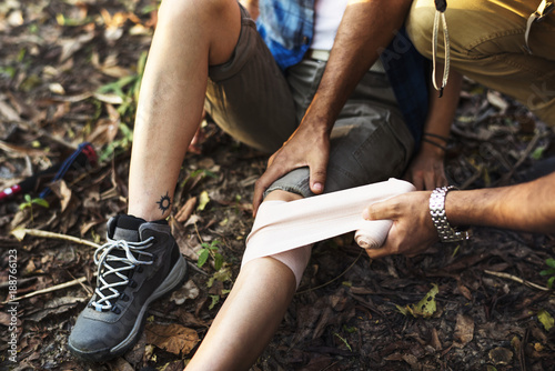 Fotografía Man putting bandage on his partner's knee in the jungle