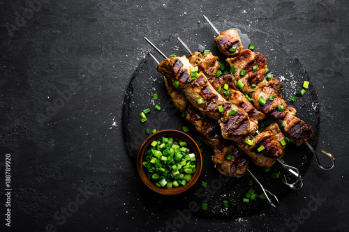 Fotografía  Grilled meat skewers, shish kebab on black background, top view