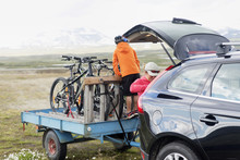 Family Preparing For Bicycle Trip With Bicycles On Car Trailer