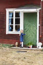 Young Blonde Girl Standing By House Green Door