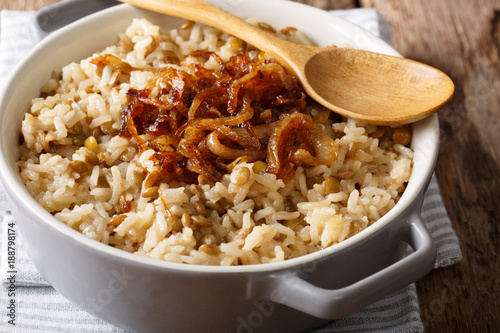 Stewed rice with lentils and fried onions close-up in a bowl. horizontal