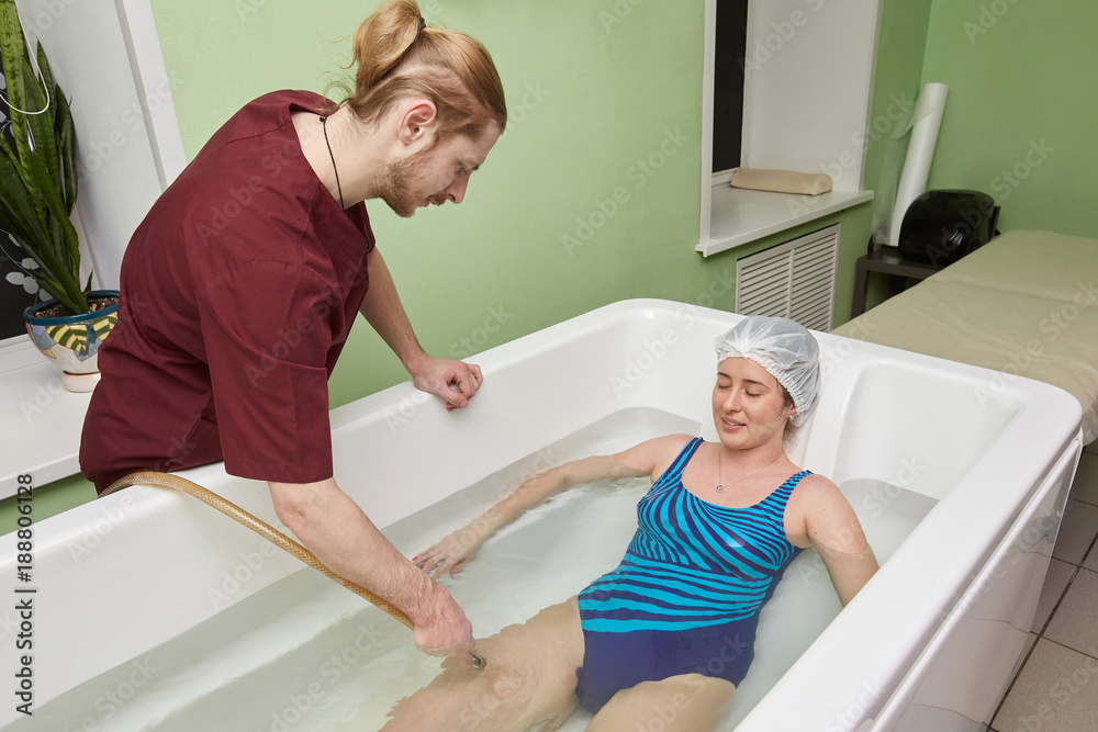 Fototapeta Young woman during hydromassage in beauty spa salon
