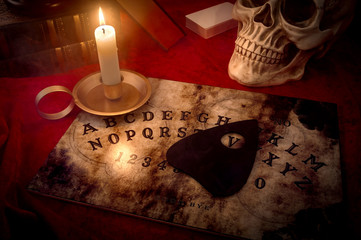 A witches den, fortune teller and black magic concept with a talking spirit board lit by a candle surrounded by a deck of cards, three books and a skull engulfed in mysterious and murky smoke