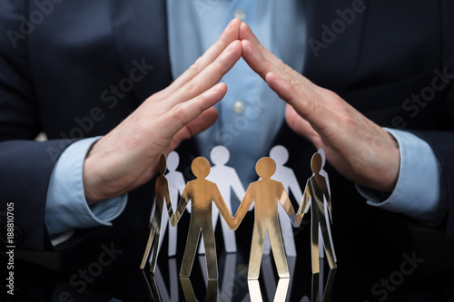 Fotografía  Businessperson Protecting Paper Cut Out People