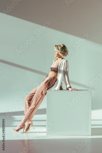 beautiful charming blonde woman in pink bra, shirt and pants sitting and looking away in studio Wall mural