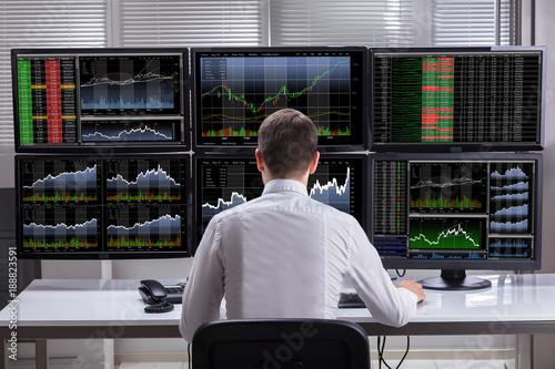 Photo  Stock Market Broker Analyzing Graphs On Computer Screens