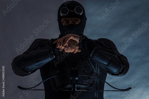 Photo  Armed spy in bulletproof vest. Hands on an arbolete.