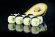 Fresh delicious Japanese sushi with avocado on dark background