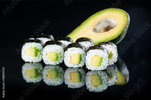 Fototapeta Fresh delicious Japanese sushi with avocado on dark background obraz