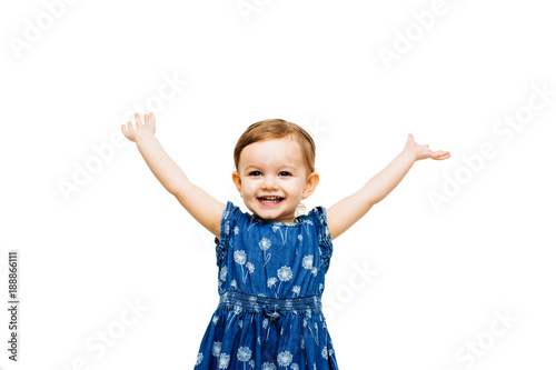 very happy toddler girl with arms outstretched up and a victorious smile