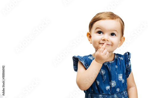 happy and curious toddler girl thinking with a finger on her mouth Wallpaper Mural
