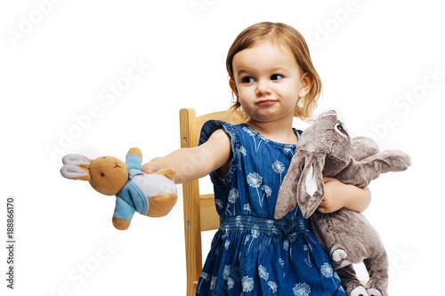 Obraz toddler girl sharing and offering a plush toy rabbit - fototapety do salonu