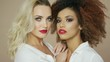 Portrait of two sensual pretty women friends with red lips looking at camera and posing in studio together.