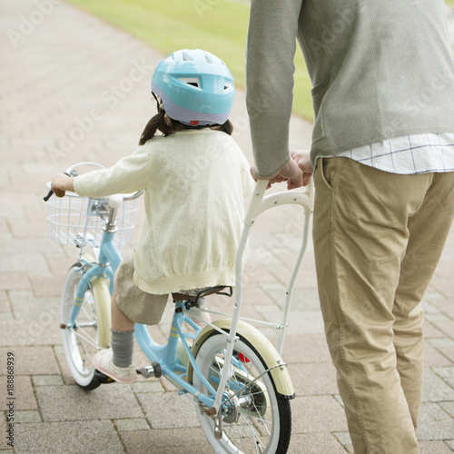 自転車の練習をする女の子と父親の後姿