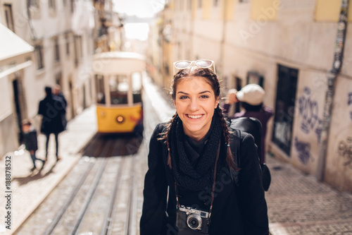 Foto  Young cheerful woman walking down the street of Lisbon